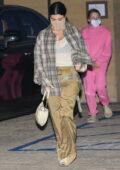 Kourtney Kardashian wears a plaid brown shirt and baggy pants for dinner at Nobu in Malibu, California