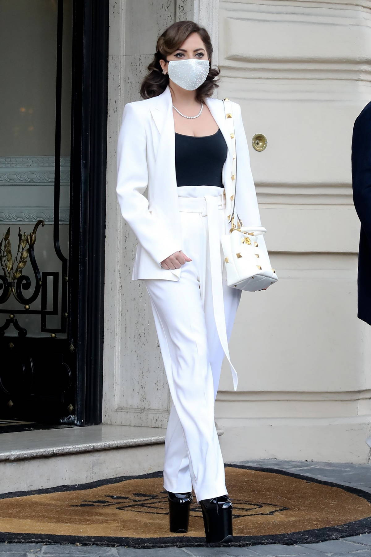 Lady Gaga looks stylish in a white pantsuit as she leaves her hotel in Rome, Italy
