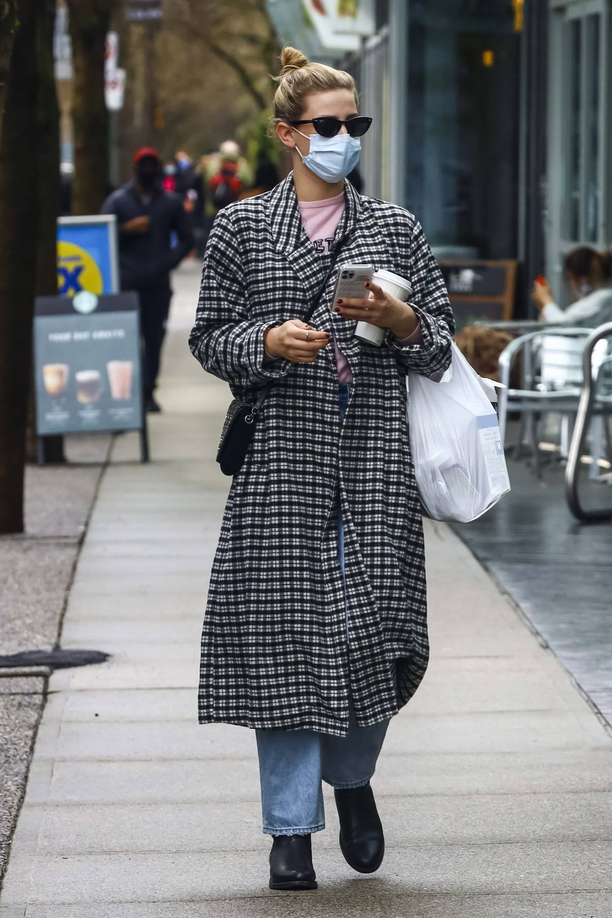 Lili Reinhart wears a black and white checkered coat as she as steps out on a coffee run in Vancouver, Canada