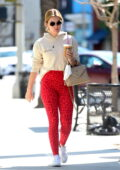 Lucy Hale sports a hoodie and red animal print leggings as she enjoys her coffee after a Pilates class in Los Angeles