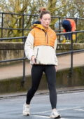 Olivia Wilde looks sporty in a quilted jacket and black leggings as she goes for a morning walk in London, UK