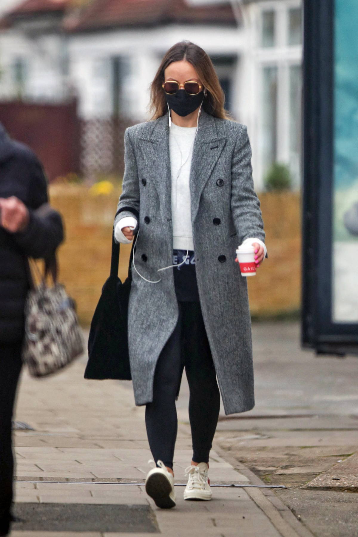 Olivia Wilde stays warm in a grey overcoat and leggings while making her morning coffee run in London, UK