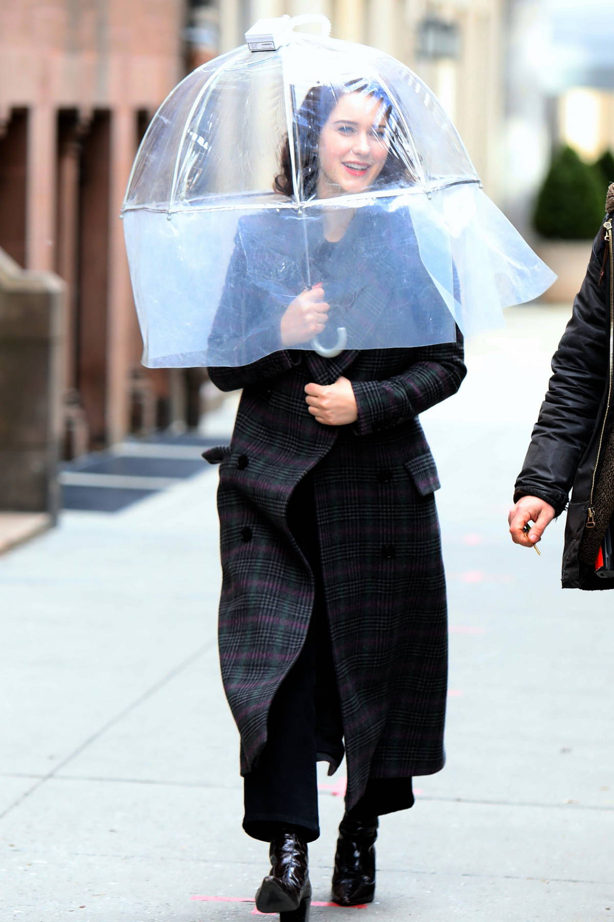 Rachel Brosnahan uses a protective clear umbrella on the set of 'The Marvelous Mrs. Maisel' in Manhattan, New York City