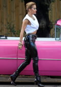 Rita Ora stuns in skin-tight leather pants while posing with a bright pink vintage car for a photoshoot in Sydney, Australia