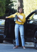 Taylor Hill goes barefoot as she carries her shoes after a trip to a nail salon in Los Angeles