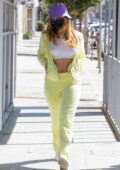 Addison Rae bares her midriff in a cropped white top with a yellow sweats while out running errands in Los Angeles