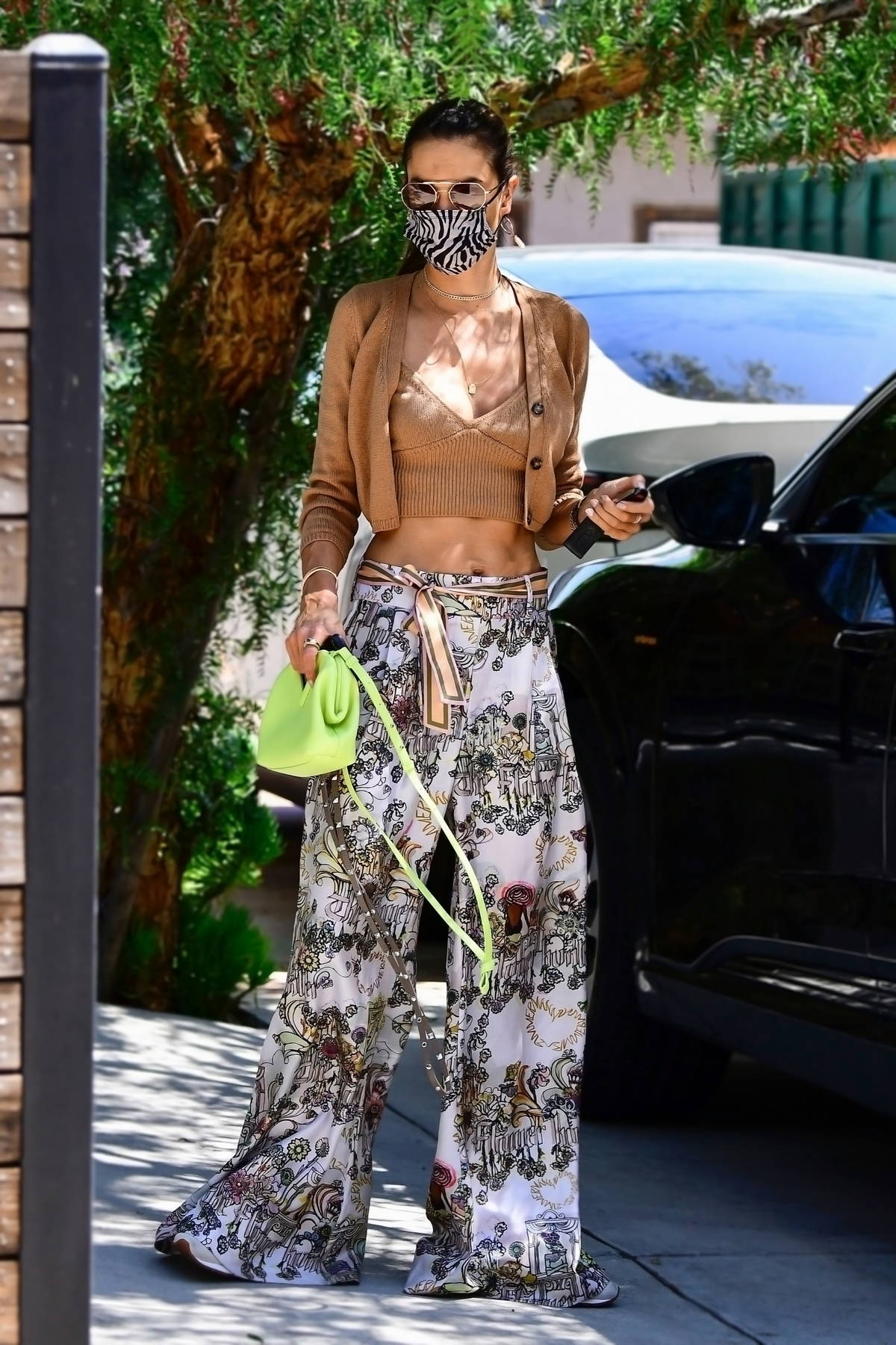 Alessandra Ambrosio flashes her toned midriff in a crop top with floral print baggy pants while out in Beverly Hills, California