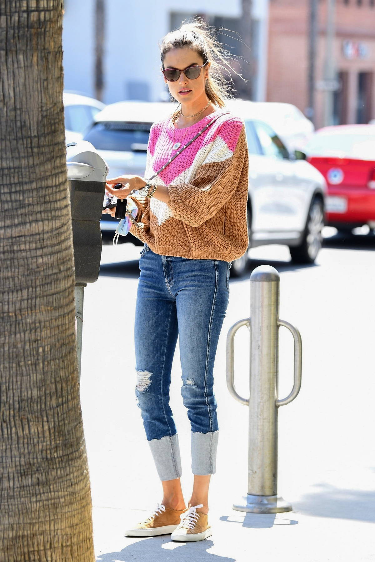 Alessandra Ambrosio rocks a colorful sweater with ripped jeans as she steps out for lunch in Santa Monica, California