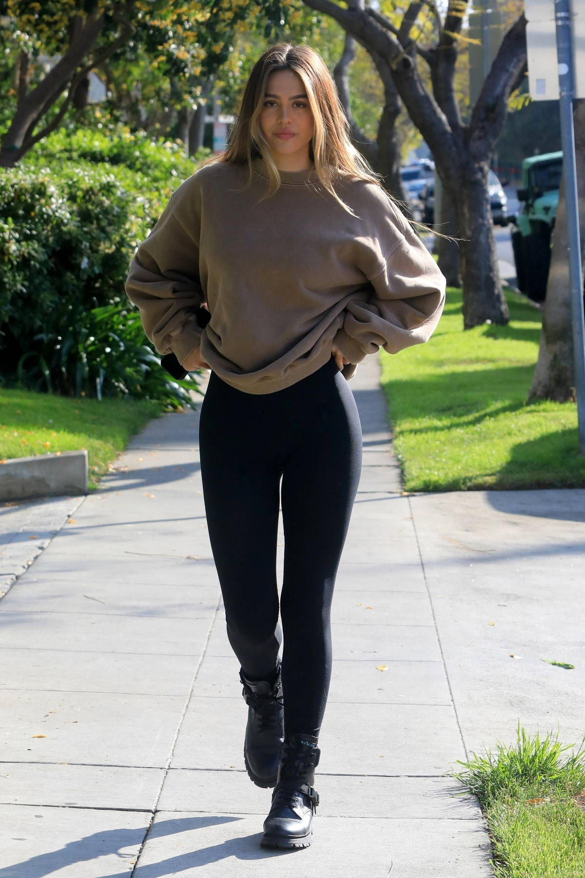 Amelia Hamlin throws a peace sign while out wearing a grey sweatshirt and black leggings in West Hollywood, California