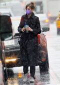 Anne Hathaway seen wearing a black trench coat while stepping out in the rain in New York City