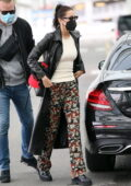 Bella Hadid looks stylish in leather trench coat and patterned pants as she leaves her hotel in Milan, Italy
