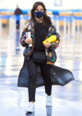 Camila Cabello dons a colorful jacket over her all-black outfit as she arrives at JFK airport in New York City