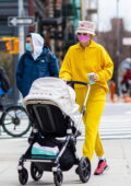 Gigi Hadid bundles up in a black puffer jacket over a bright yellow sweatsuit while out for stroll with her baby in New York City