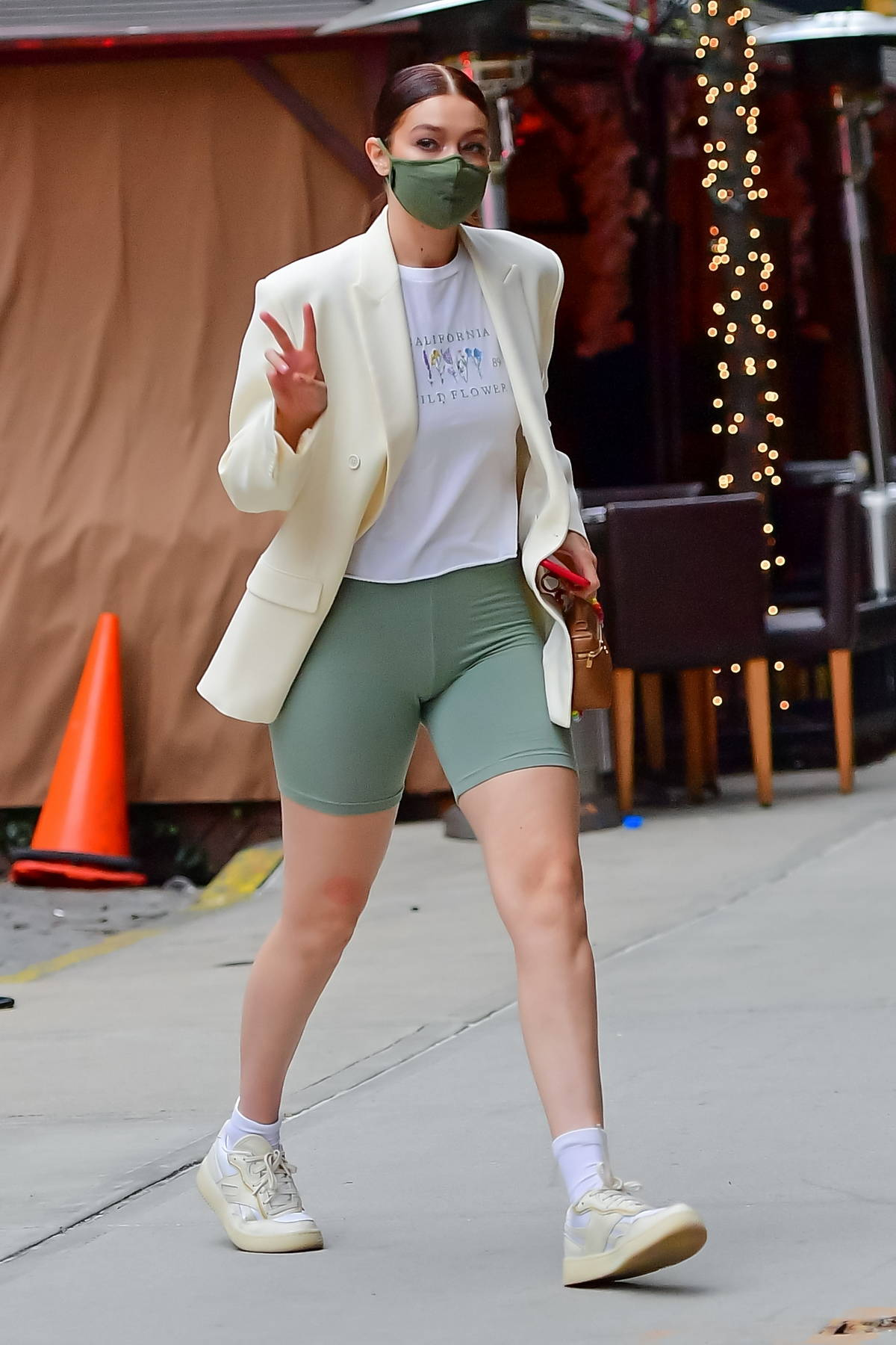 Gigi Hadid flaunts her toned legs in green legging shorts as she arrives at her apartment in New York City
