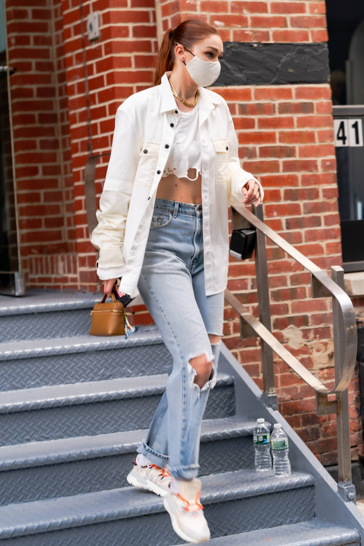 Gigi Hadid looks trendy in an unbuttoned white shirt with a crop top with ripped jeans while heading out in New York City