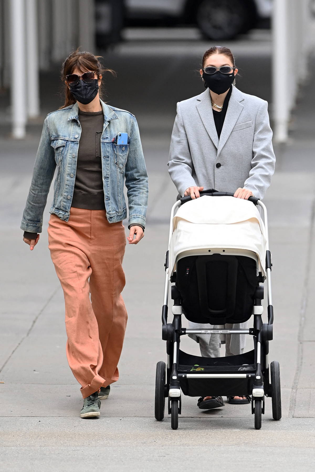 Gigi Hadid out seen wearing a grey overcoat while out for a stroll with her daughter and Helena Christensen in New York City