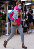 Gigi Hadid sports a pink and blue hoodie with a denim vest and grey sweatpants for a solo outing in New York City