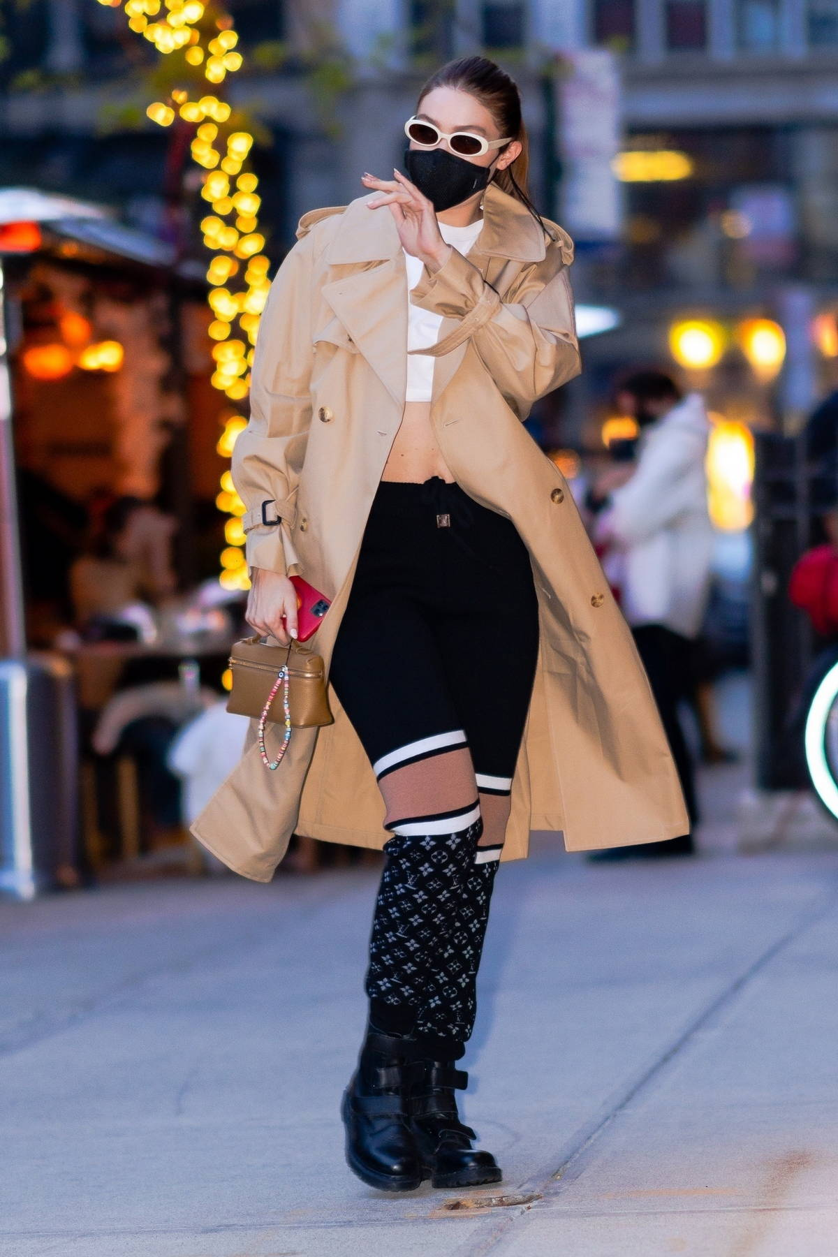 Gigi Hadid waves for the camera as she returns home from a day shooting for Maybelline in New York City