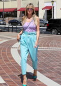 Heidi Klum wears baggy jeans and a purple tank top as she arrives at America's Got Talent taping in Los Angeles