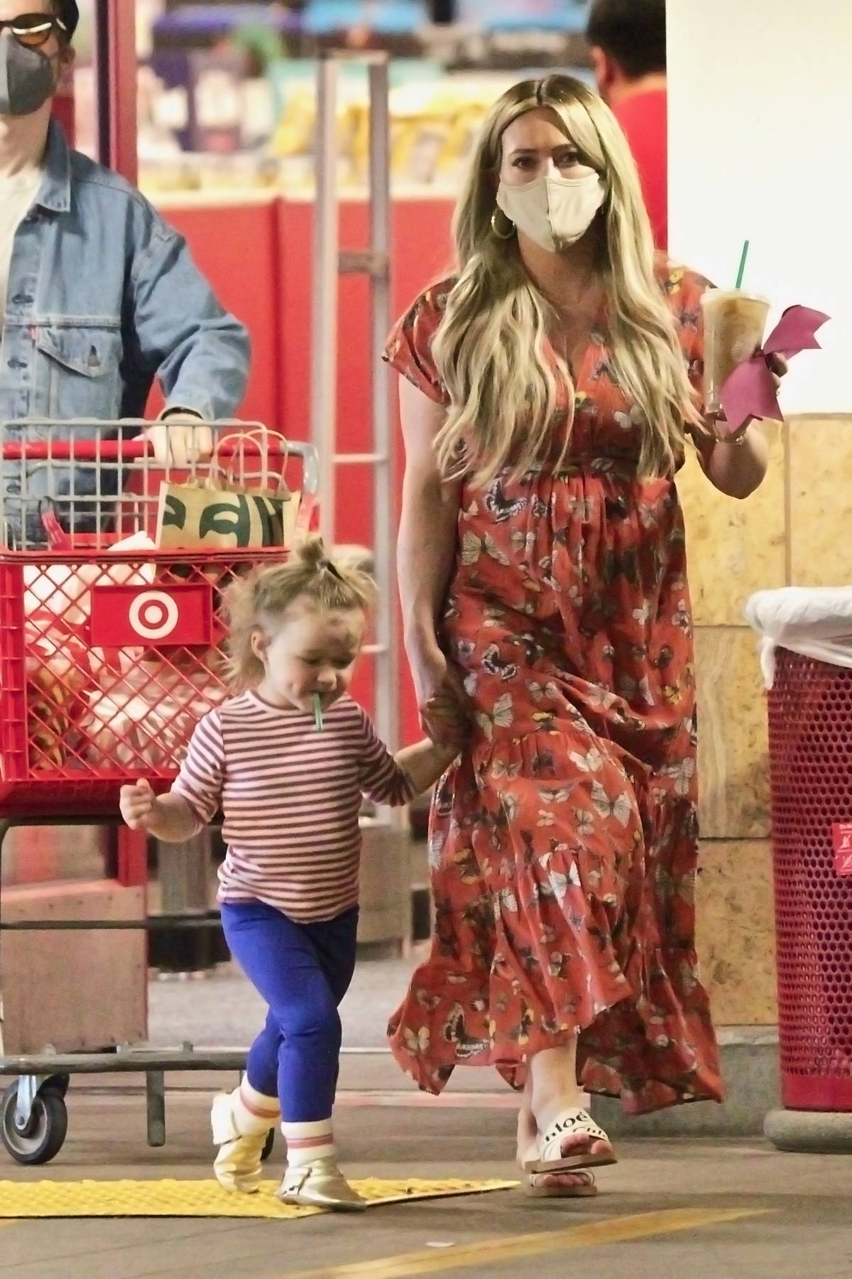 Hilary Duff wears a red butterfly print dress while shopping with her family at Target in Los Angeles