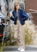 Kaia Gerber is all smiles as she steps out wearing a blue jacket with khaki trousers in West Hollywood, California