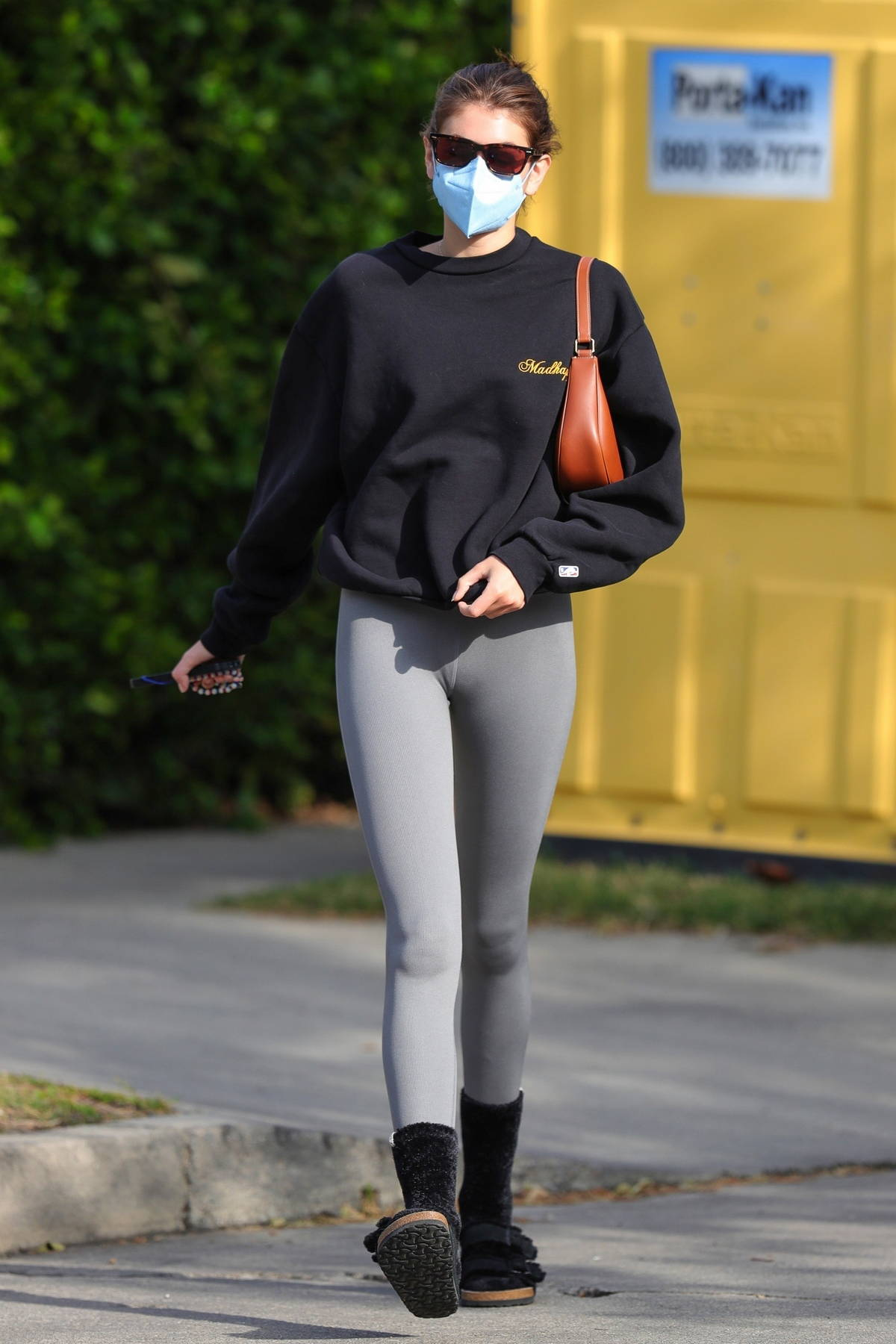 Kaia Gerber wears a black sweatshirt and grey leggings as she leaves after her Pilates class in West Hollywood, California