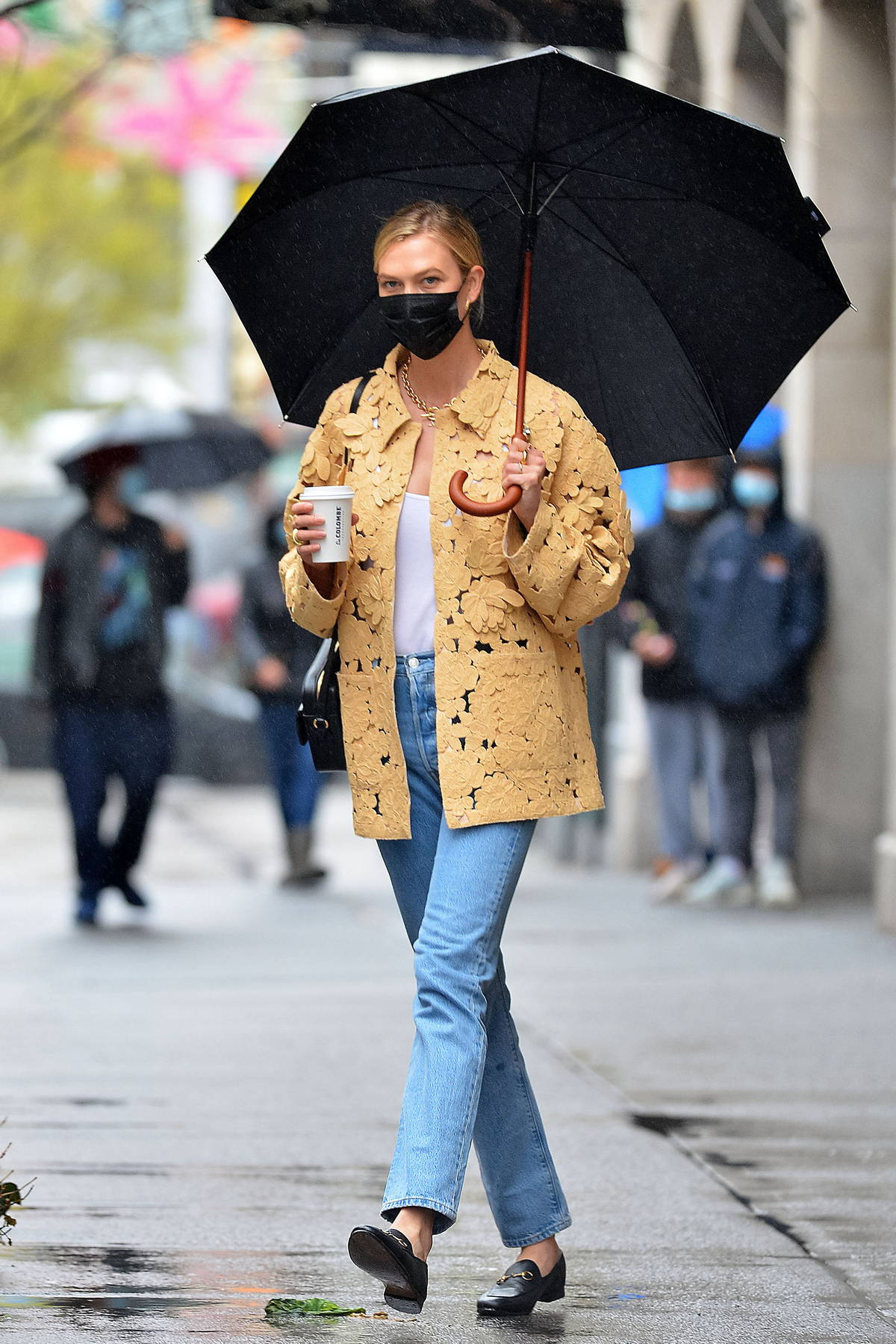 Karlie Kloss dons a stylish floral jacket as she steps out in the rain for a coffee in New York City