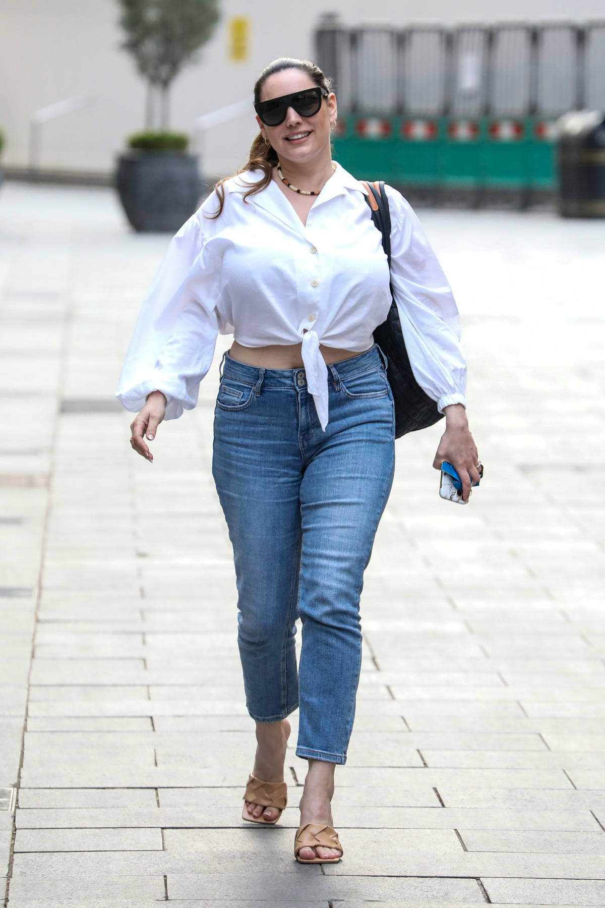 Kelly Brook flashes a smile and her midriff as she leaves her Heart FM show at the Global Radio Studios in London, UK