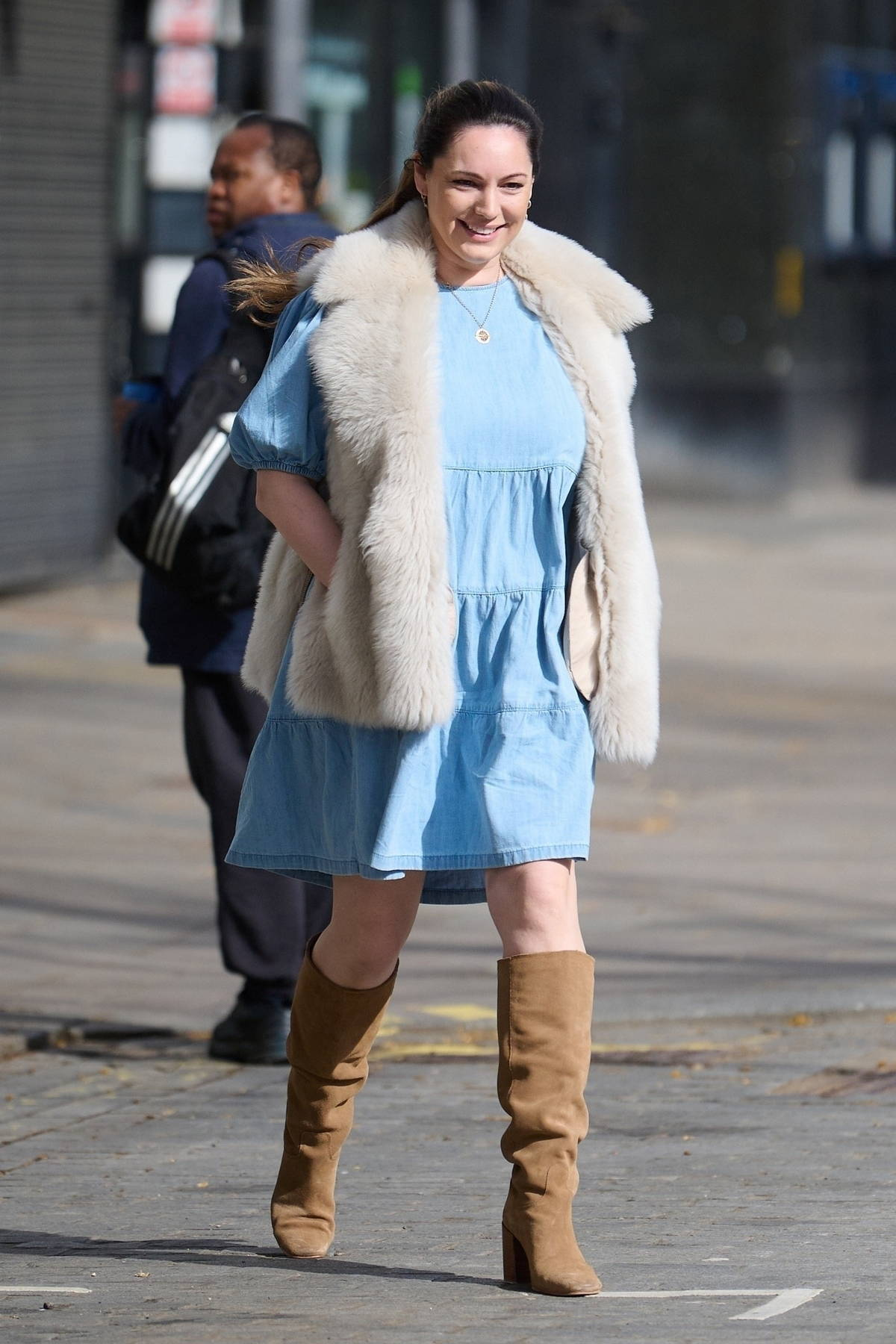 Kelly Brook is all smiles as she leaves Global Radio Studios wearing a blue dress and knee-high suede boots in London, UK