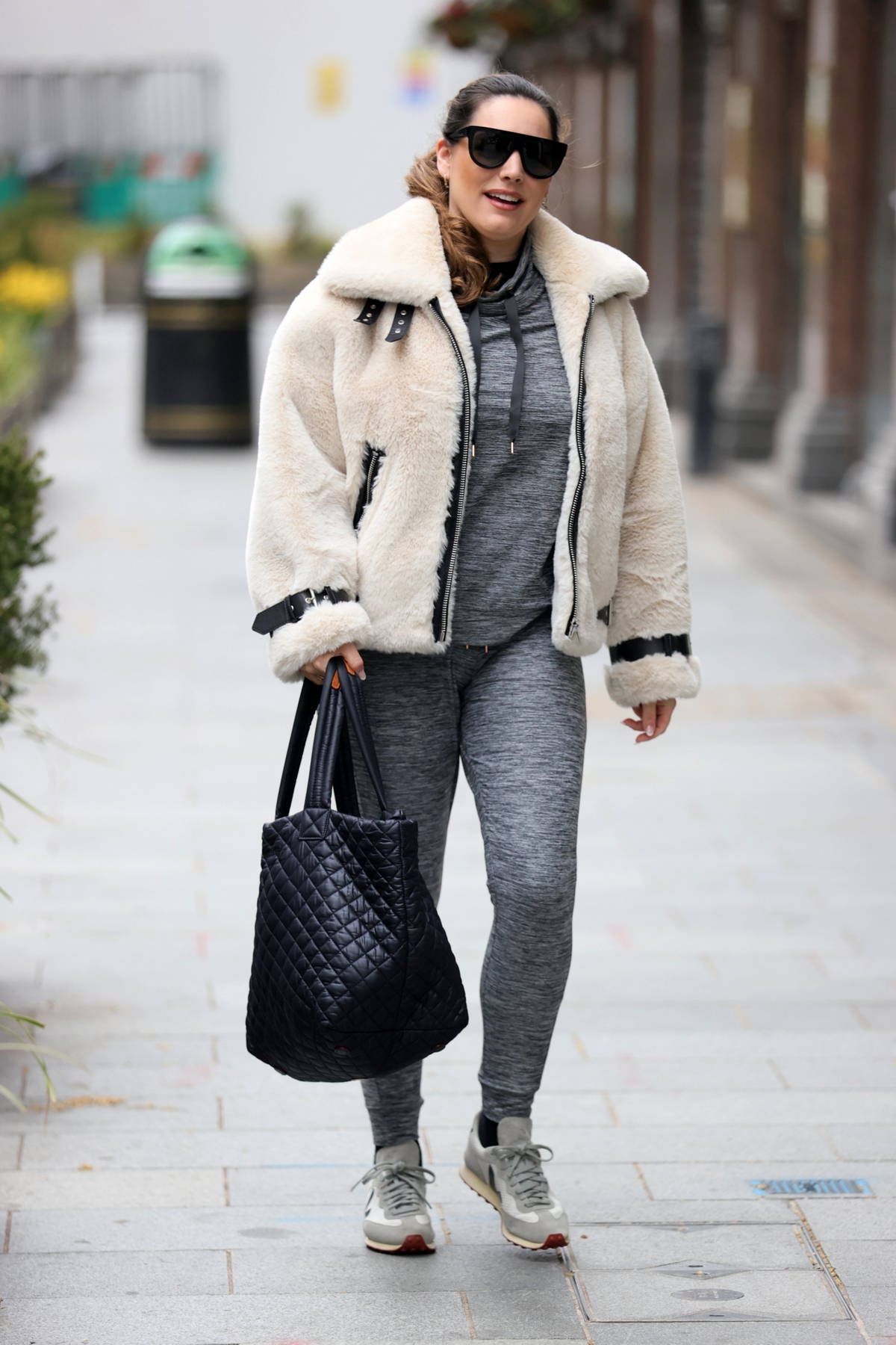 Kelly Brook wears a cream fur jacket over grey sweats while arriving for her Heart Radio show in London, UK