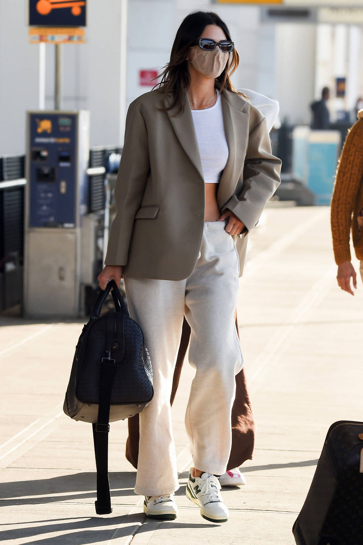 Kendall Jenner looks casually chic in a blazer over a crop top as she arrives at the JFK Airport in New York