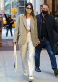 Kendall Jenner looks stylish a beige blazer with white crop top and trousers as she checks out of Four Seasons in New York City