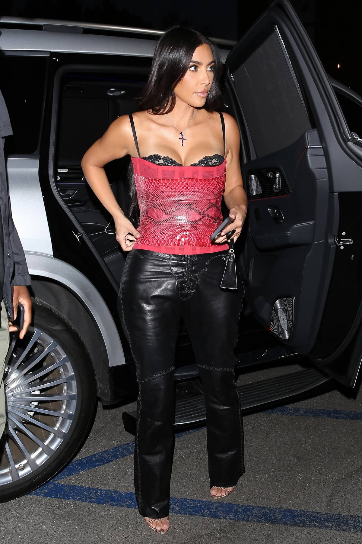 Kim Kardashian rocks a red corset and black leather pants as she steps out to dinner with friends in Brentwood, California