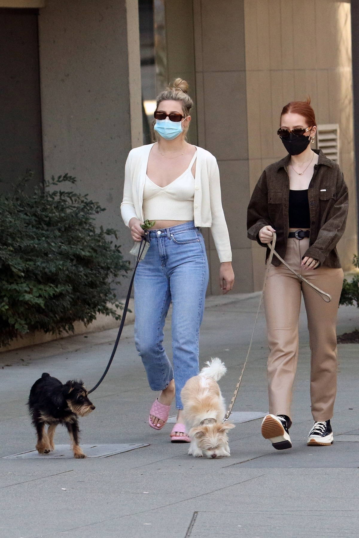 Lili Reinhart wears a cream crop top as she takes a walk with Madelaine Petsch in Vancouver, Canada
