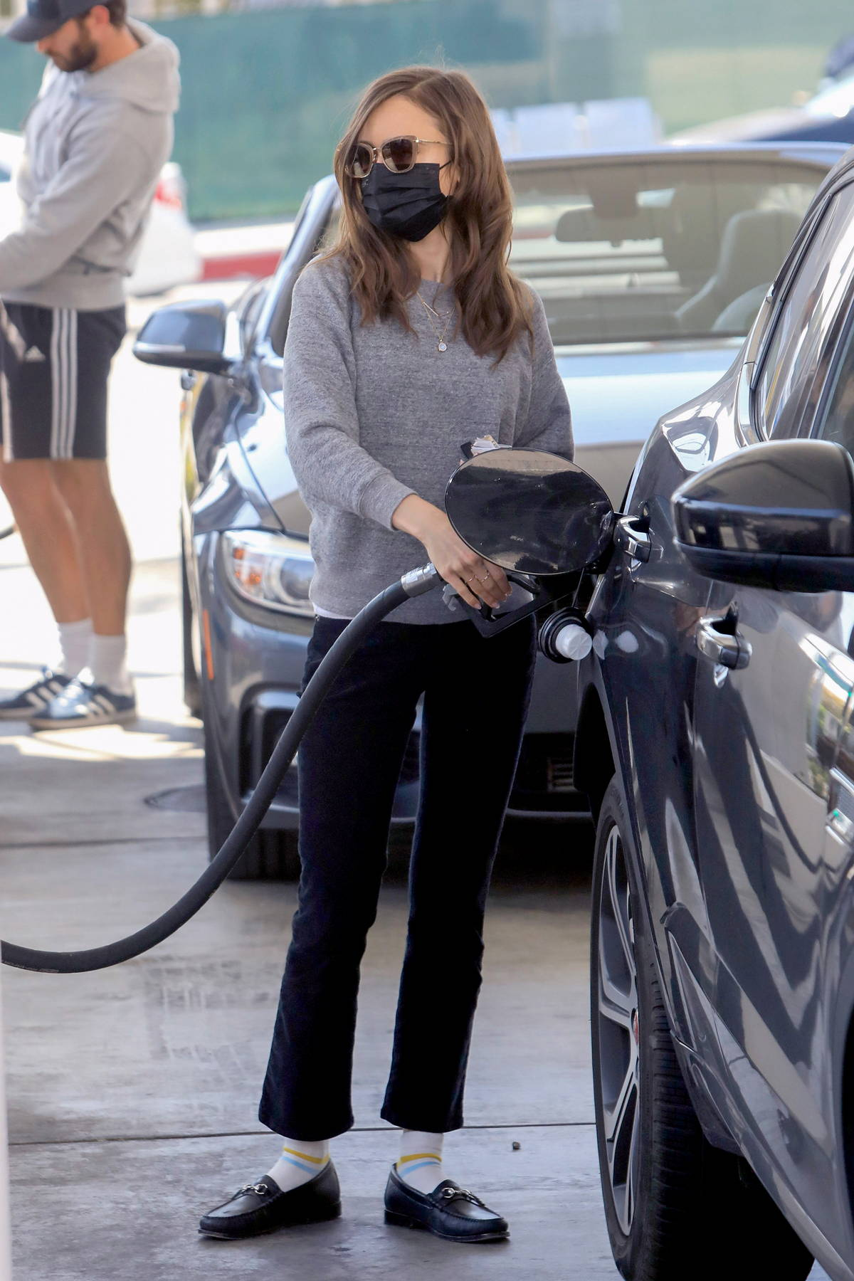 Lily Collins keeps it casual in a grey sweater and black trousers while pumping gas in West Hollywood, California
