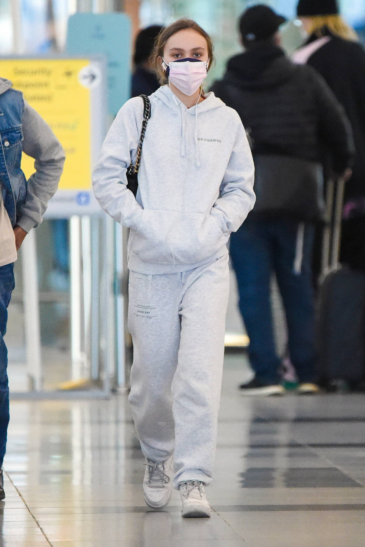 Lily-Rose Depp wears a hoodie and sweatpants with two face masks as she arrives at JFK Airport in New York City
