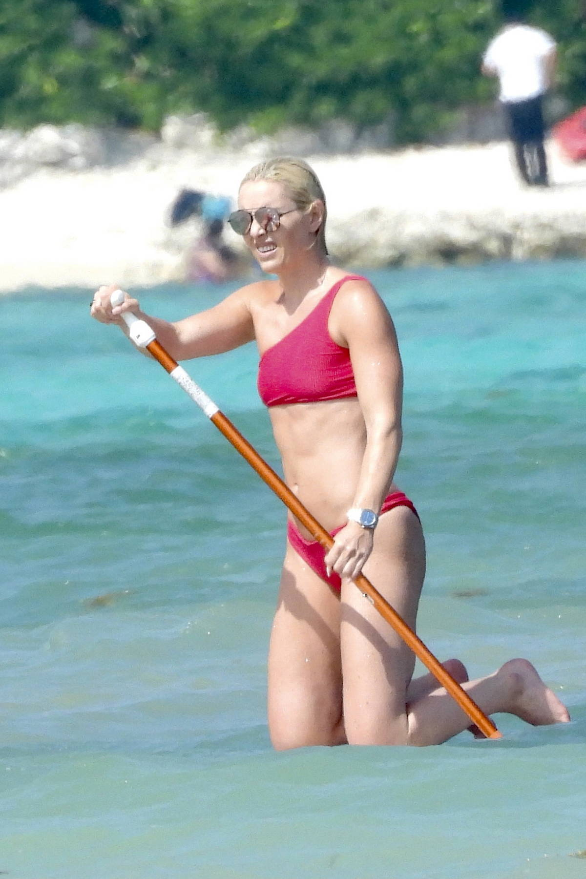 Lindsey Vonn shows off her athletic figure in a red bikini as she enjoys some paddle-boarding while on vacation in Tulum, Mexico