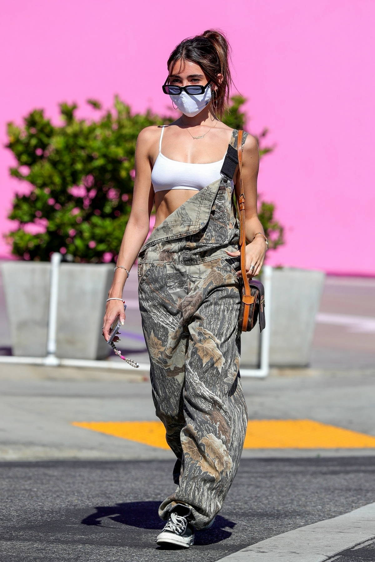 Madison Beer looks cute in camo overalls and a white sports bra while out for late lunch in West Hollywood, California