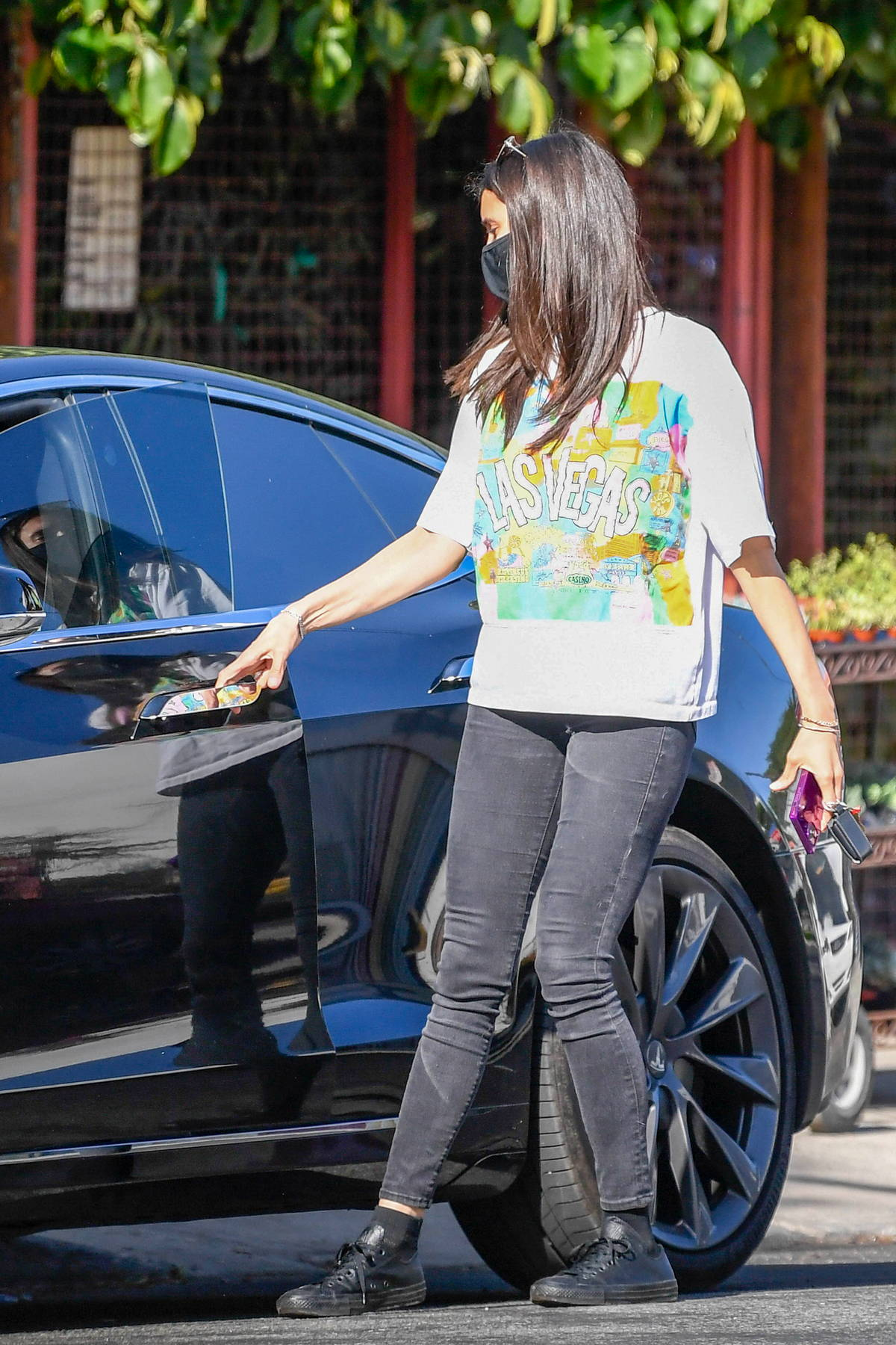 Nina Dobrev wears a colorful graphic print tee while visiting a nursery in Los Angeles
