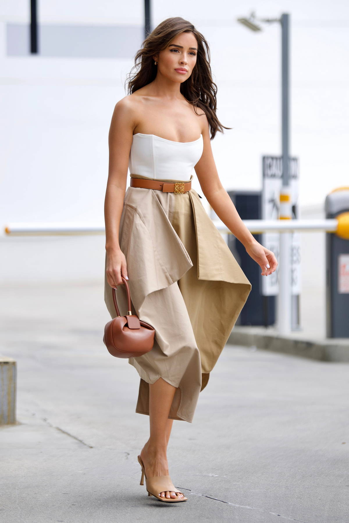 Olivia Culpo looks flawless in a white tube top and beige skirt as she leaves a business meeting in Beverly Hills, California