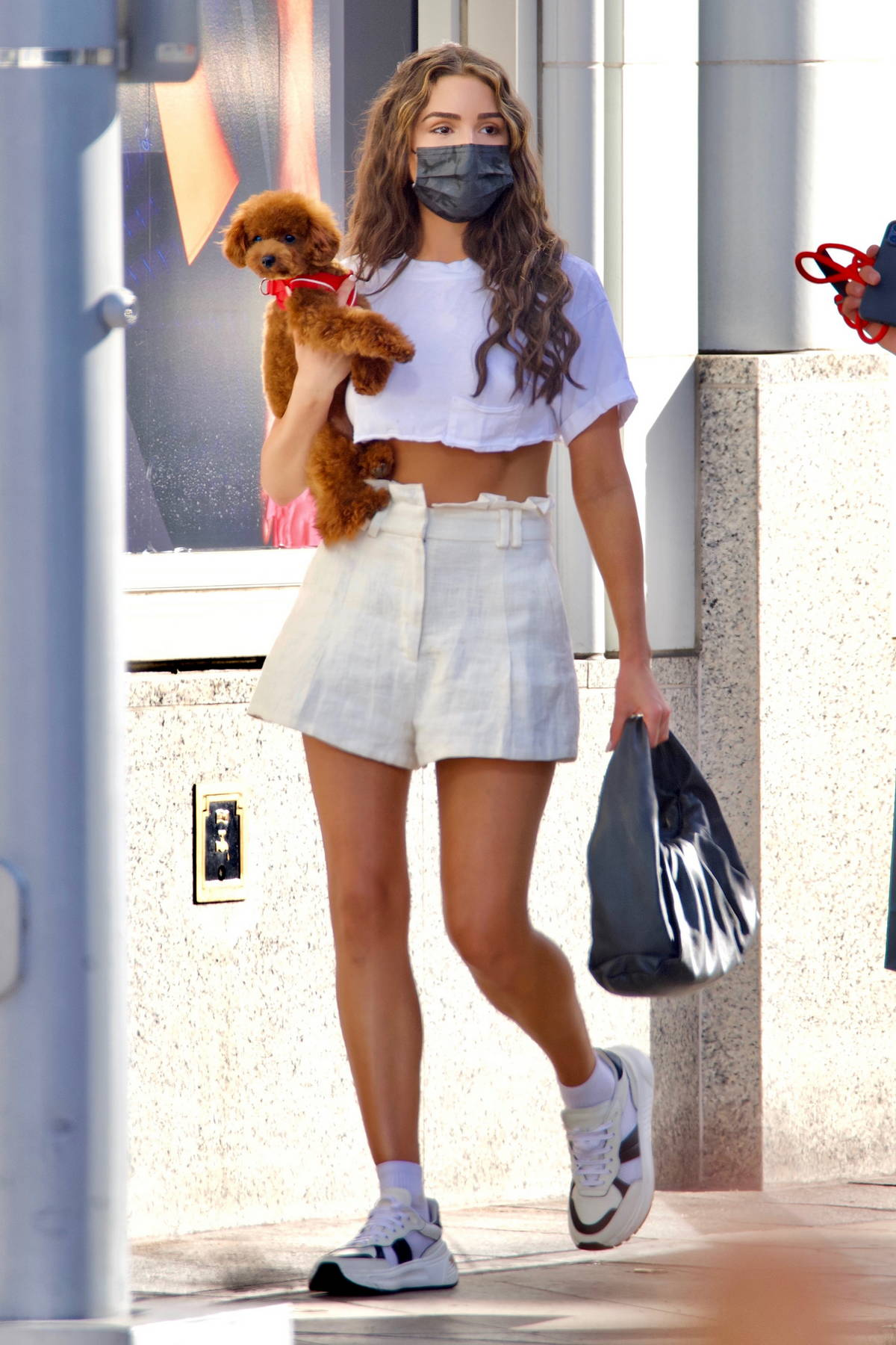 Olivia Culpo shows off her summer style in a cropped white tee and shorts while out with her puppy in Beverly Hills, California