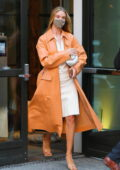 Rosie Huntington-Whiteley looks fashionable in an orange trench coat over a white dress while heading out in New York City