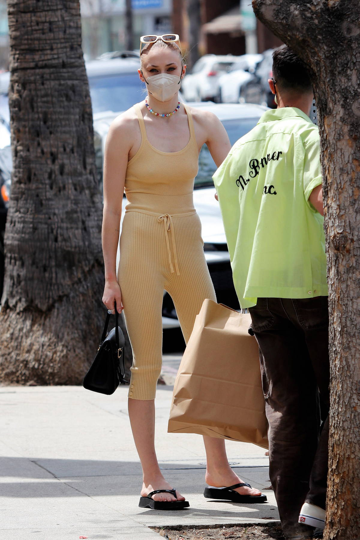 Sophie Turner sports a beige tank top with matching joggers while out shopping with Joe Jonas and their baby in Los Angeles