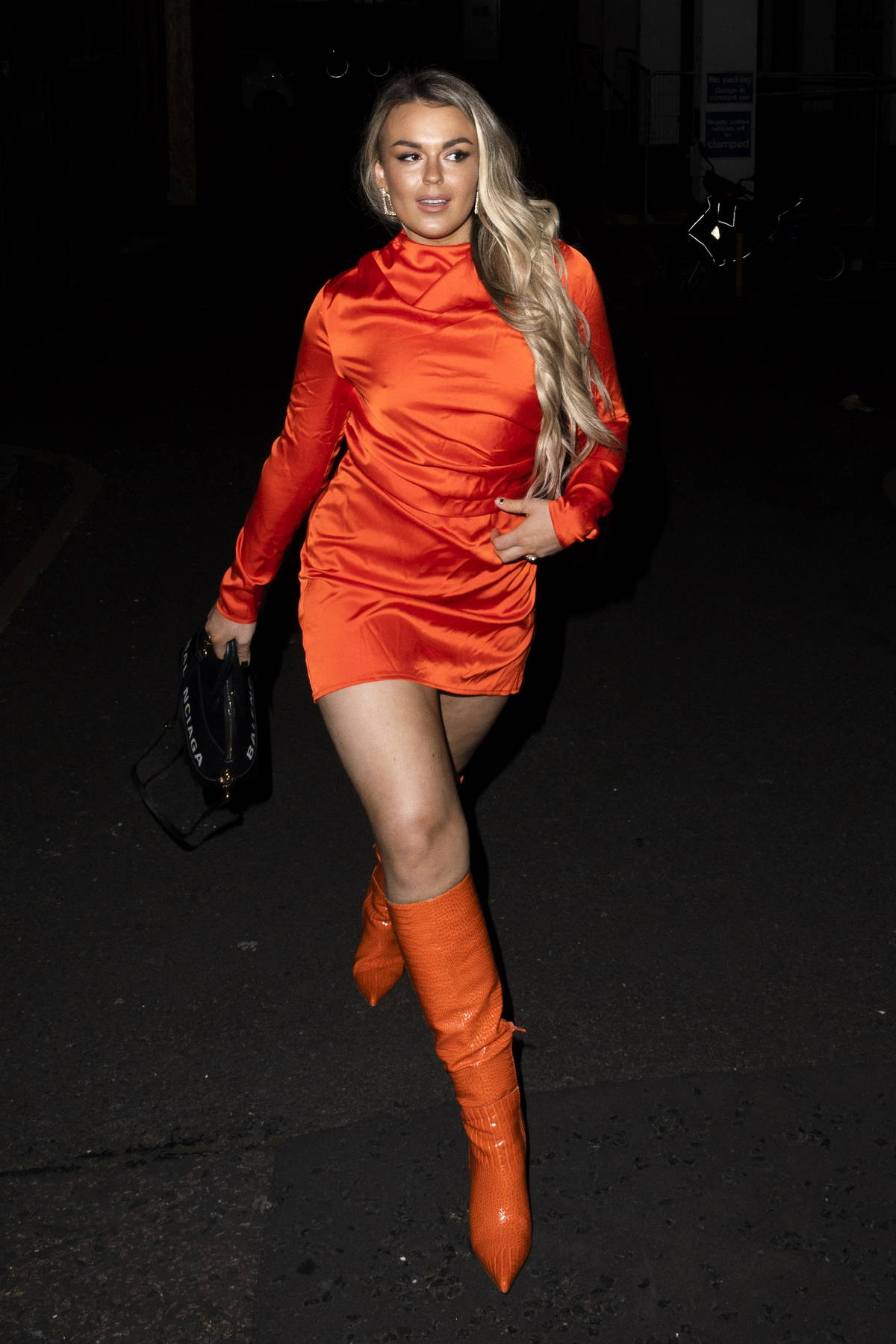 Tallia Storm looks striking in a bright orange mini dress with matching knee-high boots during a night out in London, UK