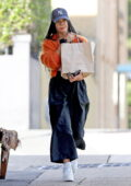 Tessa Thompson grabs some lunch wearing an orange Cardigan and New York Cap with platform trainers in Sydney, Australia