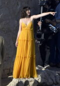 Ana de Armas seen wearing a yellow maxi dress on the rocks of a beach during the filming of an ad in Mallorca, Spain