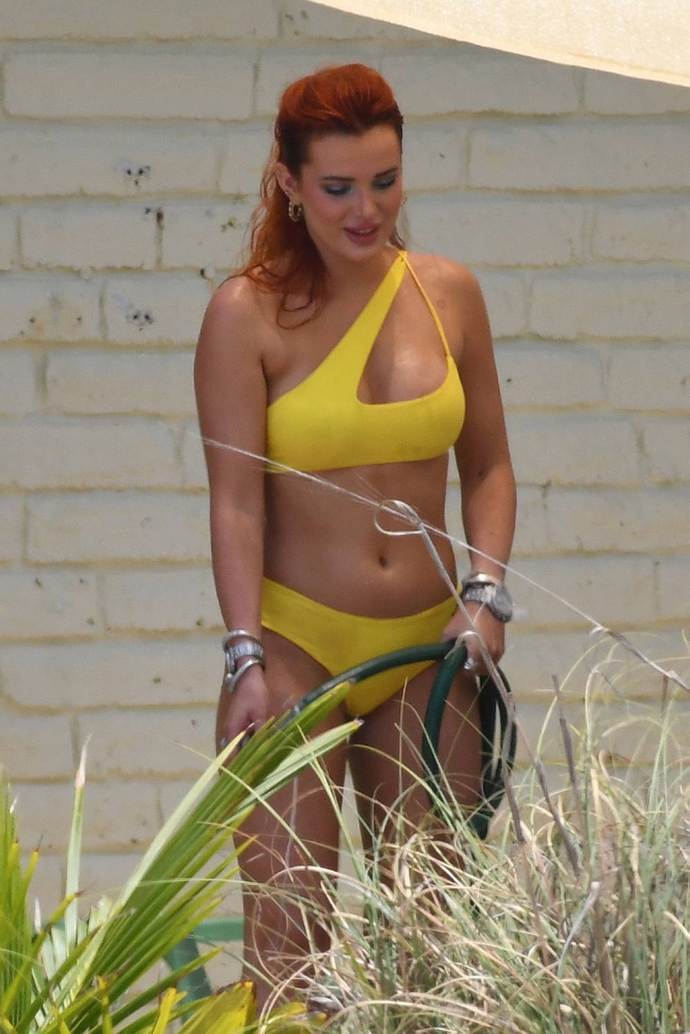 Bella Thorne sizzles in a yellow bikini while posing with a garden hose for a photoshoot in Miami, Florida