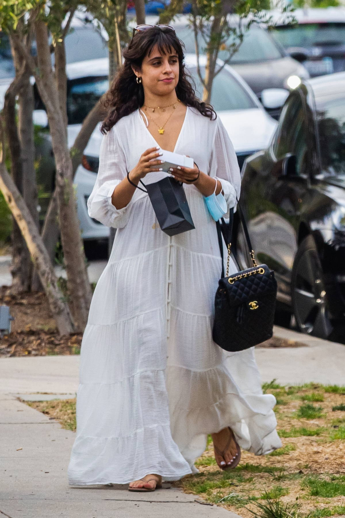 Camila Cabello looks radiant in a flowing white dress while out shopping with a friend in Los Angeles