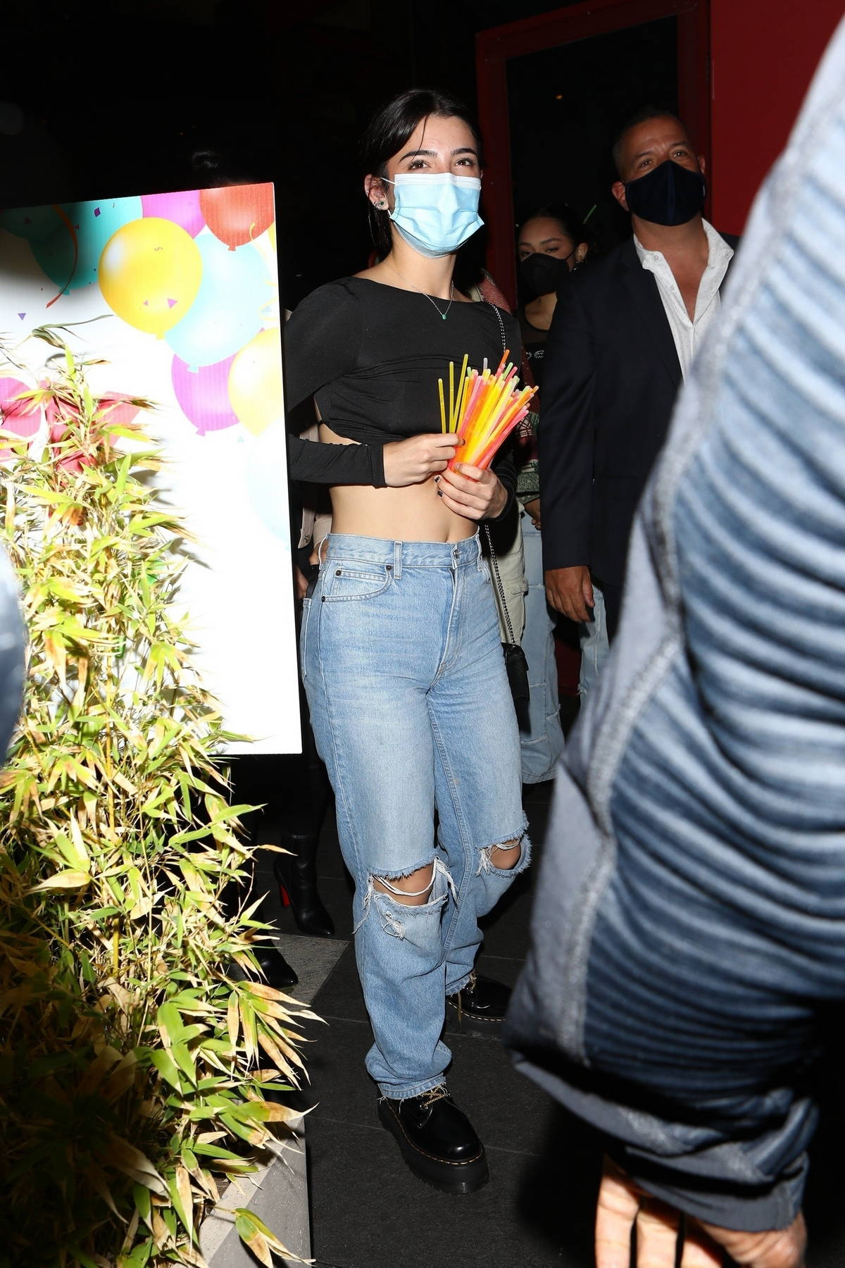 Charli D'Amelio wears a black crop top and ripped jeans as she arrives at Noah Beck's birthday in West Hollywood, California