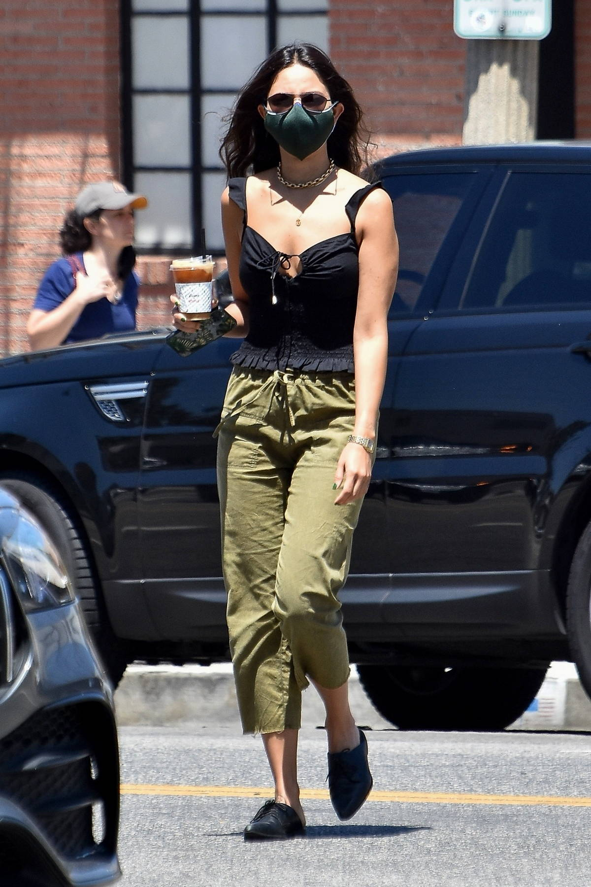 Eiza Gonzalez wears a black top and green drawstring pants while making a coffee run in West Hollywood, California